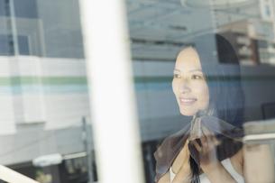 お風呂上がりで窓の外を眺める笑顔の20代女性の写真素材 [FYI04501441]
