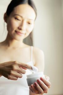 部屋で化粧品を塗ろうとする20代女性の写真素材 [FYI04501444]