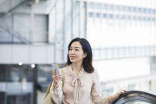 エスカレーターに乗る女性の写真素材 [FYI04501642]