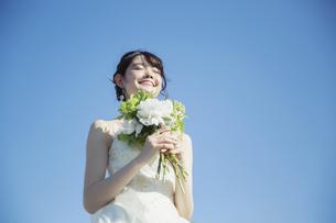 青空の下に立つウエディングドレス姿の20代女性の写真素材 [FYI04501857]