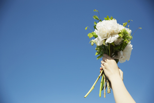 ブーケを空に掲げる女性の手元の写真素材 [FYI04501862]