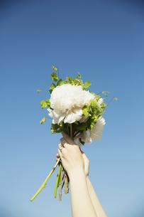 ブーケを空に掲げる女性の手元の写真素材 [FYI04501863]