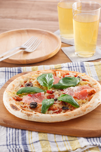 生ハムとバジルのピザのある食卓の写真素材 [FYI04502970]