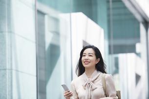 スマートフォンを持ちながら歩く女性の写真素材 [FYI04503221]