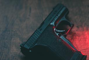 赤い光に照らされた拳銃の写真素材 [FYI04503244]