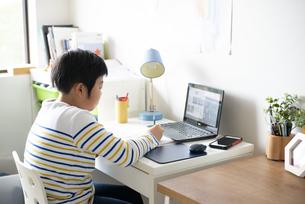 自宅でパソコンの前で勉強をしている男の子の写真素材 [FYI04504061]
