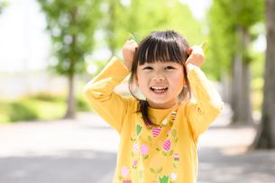 葉っぱで遊ぶ女の子の写真素材 [FYI04505478]