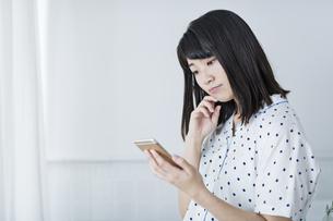 女性 携帯電話 悩むの写真素材 [FYI04506172]