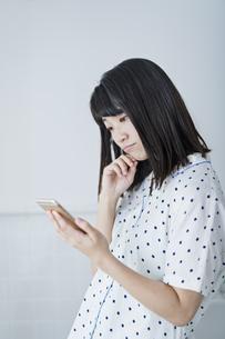 女性 携帯電話 悩むの写真素材 [FYI04506173]