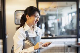 カフェで注文をとる20代女性の写真素材 [FYI04506469]