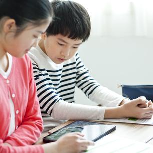 タブレットPCを使って勉強する小学生の写真素材 [FYI04507295]