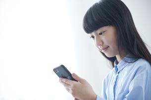 スマートフォンを見る小学生の写真素材 [FYI04507349]