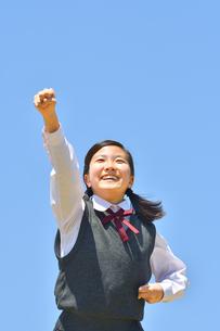 青空でガッツポーズをする女の子の写真素材 [FYI04507520]