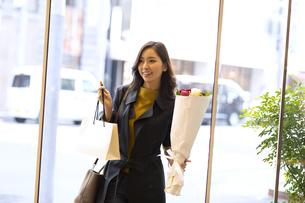 花束を持って入店する女性の写真素材 [FYI04508058]