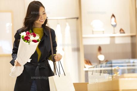 お店で花束を持ってショーケースを見る女性の写真素材 [FYI04508060]