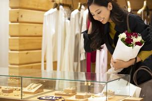 お店で花束を持ってショーケースを見る女性の写真素材 [FYI04508061]