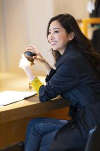 カウンターでコーヒーを手に持つ女性の写真素材 [FYI04508063]