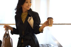 新聞を小脇にカバンとカップを持つ女性の写真素材 [FYI04508064]