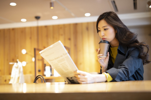 カウンターで新聞を読む女性の写真素材 [FYI04508068]
