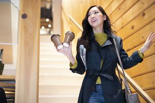 階段でコーヒーを持つ女性の写真素材 [FYI04508069]