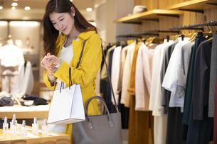 お店で香水を試す女性の写真素材 [FYI04508070]