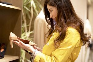 お店で靴を選ぶ女性の写真素材 [FYI04508071]