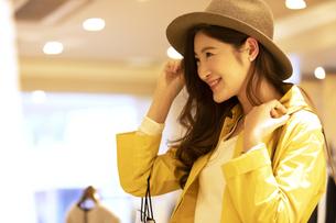 お店で帽子を選ぶ女性の写真素材 [FYI04508073]