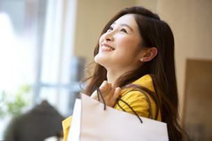 ショッピングバックを持って見上げる女性の写真素材 [FYI04508074]