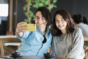 カフェで写真を撮る男女の写真素材 [FYI04508768]