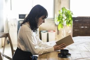 カフェで読書をする女性の写真素材 [FYI04508777]