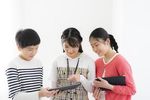 タブレットPCを見ながら談笑する小学生の写真素材 [FYI04508850]