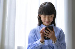 スマートフォンを見る小学生の写真素材 [FYI04508909]