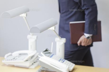 オフィスの電話と社内を歩く男性の写真素材 [FYI04510558]