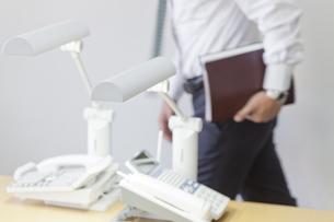 オフィスにある電話と社内を歩く男性の写真素材 [FYI04510560]