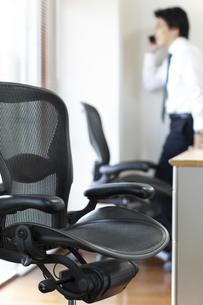 オフィスにある椅子と電話をかける男性社員の写真素材 [FYI04510561]