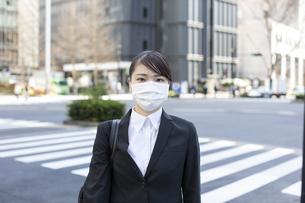交差点でマスクをした若い女性の写真素材 [FYI04510667]