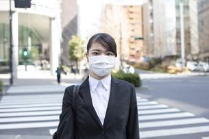 ビジネス街でマスクをした若い女性の写真素材 [FYI04510669]