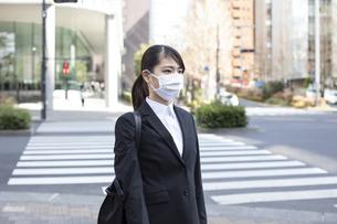 歩道でマスクをした若い女性の写真素材 [FYI04510671]