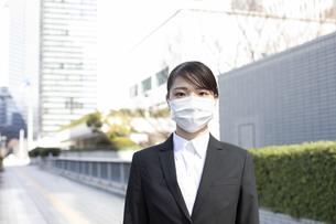 ビジネス街でマスクを着用する若い女性の写真素材 [FYI04510672]