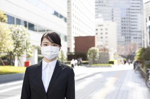 路上でマスクを着用する若い女性の写真素材 [FYI04510673]