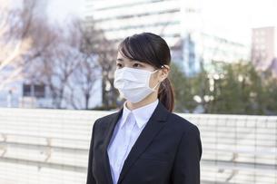 オフィス街でマスクをしたビジネスウーマンの写真素材 [FYI04510677]