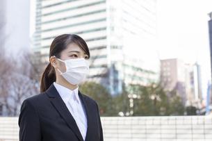 ビジネス街でマスクをしたスーツ姿の若い女性の写真素材 [FYI04510679]