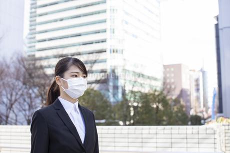 ビジネス街でマスクをしたスーツ姿の若い女性の写真素材 [FYI04510680]