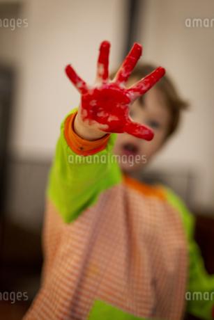赤色のペイントを手につけて、あそぶ子供。の写真素材 [FYI04511099]