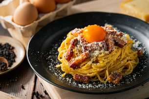 Delicious pasta carbonara on black plate.の写真素材 [FYI04511771]