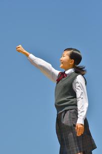 青空でガッツポーズをする女の子の写真素材 [FYI04513057]