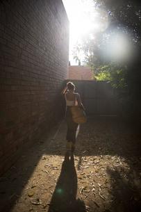 サマードレスを着て、カゴを肩にかけて陽の光を受けながら歩く女性の後ろ姿の写真素材 [FYI04513167]
