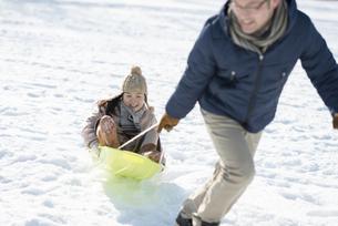 父親とそり遊びをする女の子の写真素材 [FYI04514080]
