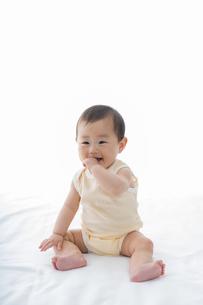 白いシーツの上でお座りしている笑顔の赤ちゃんの写真素材 [FYI04516148]