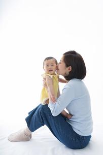 ママの膝に乗り、ホッペにキスされて喜ぶ赤ちゃんの写真素材 [FYI04516153]